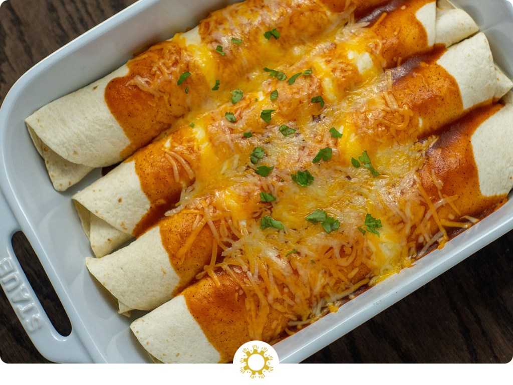 4 baked chicken enchiladas drizzled with enchilada sauce and topped with shredded cheese and cilantro in a white casserole dish on a wooden surface (with logo overlay)