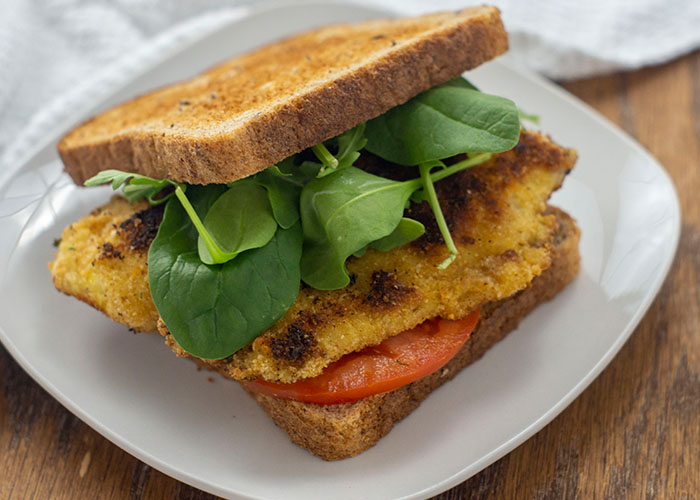 Fried tilapia sandwich wiht sliced tomato and fresh spinach on a square white plate with a white towel behind on a wooden surface