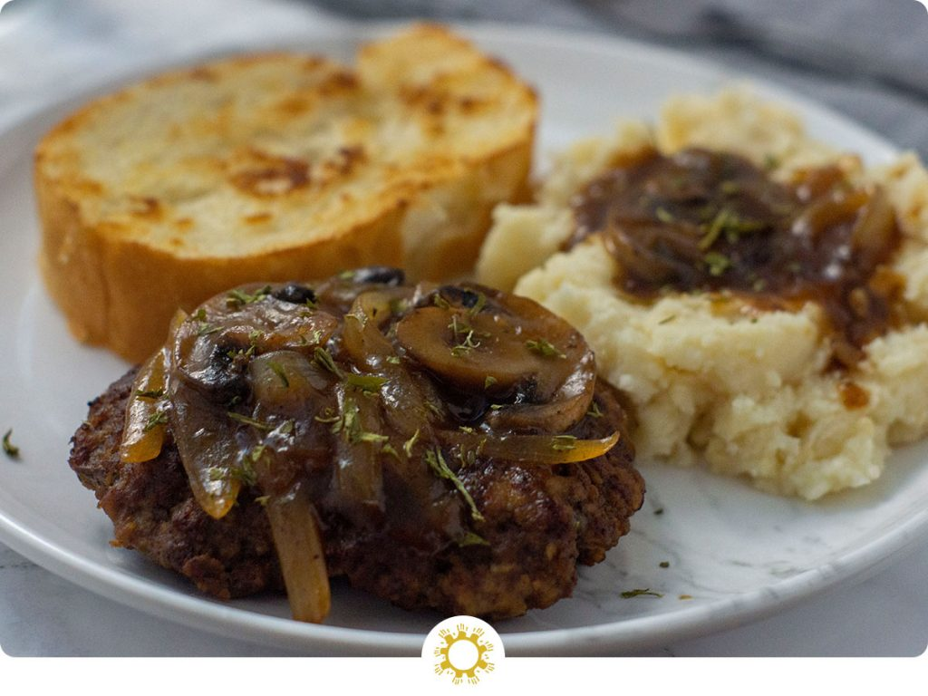 Salisbury Steak with mashed potatoes covered with salisbury gravy and a piece of garlic toast on a round white plate with a grey napkin and fork behind all on a white and grey marble surface (with logo overlay)