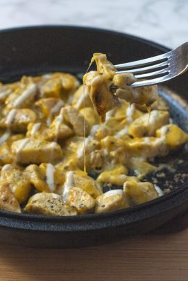 Metal fork lifting a piece of cheesy chicken and ranch from a cast iron skillet with the remaining meat on a wooden surface (vertical)