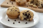 Two chocolate chip muffins, one with a bite missing, on a round white plate with a few extra chocolate chips with a bamboo tray of chocolate chip muffins behind it all on a white and grey marble surface