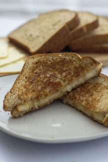 Classic Grilled Cheese Sandwich wedges on a round white plate with sliced bread and cheese behind all on a white surface (vertical)