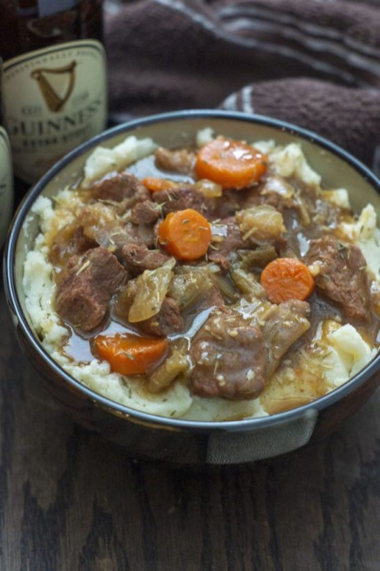 Guinness Beef Stew over a bed of mashed potatoes in a brown bowl with a bottle of Guinness beer and a brown and white towel behind all on a wooden surface (vertical)