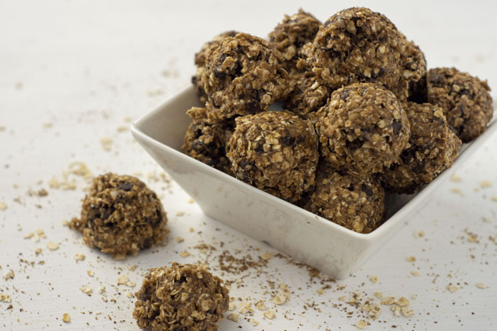 Oatmeal Energy Balls in a square bowl with a few next to the bowl on a white surface sprinkled with oats, flax seed, and chia seeds