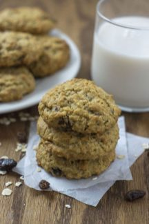 Three oatmeal raisin cookies stacked on pieces of parchment paper with oats and raisins around them with a plate of cookies and a glass of milk behind all on a wooden surface (vertical)