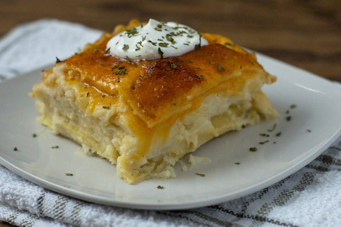 Square cut of pierogi lasagna topped with sour cream and seasonings on a round white plate on a white and grey towel all on a wooden surface