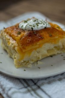 Square cut of pierogi lasagna topped with sour cream and seasonings on a round white plate on a white and grey towel all on a wooden surface (vertical)