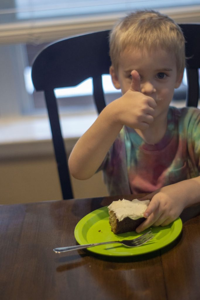 Young boy giving a thumbs up with a banana bread bar on a green plate