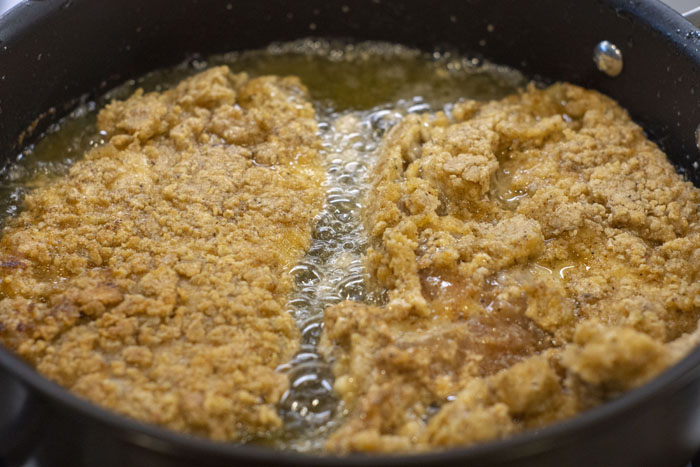 Breaded chicken breast frying in oil in a large skillet
