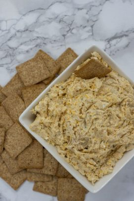 Cheesy Ranch Chicken Dip in a square white bowl next to a pile of square crackers on a white and grey marble surface (vertical)
