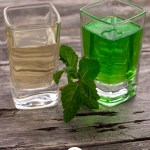 Two square glass shot glasses with clear creme de menthe in one and green creme de menthe in the other with a sprig of mint between on a wooden surface (vertical with title overlay)