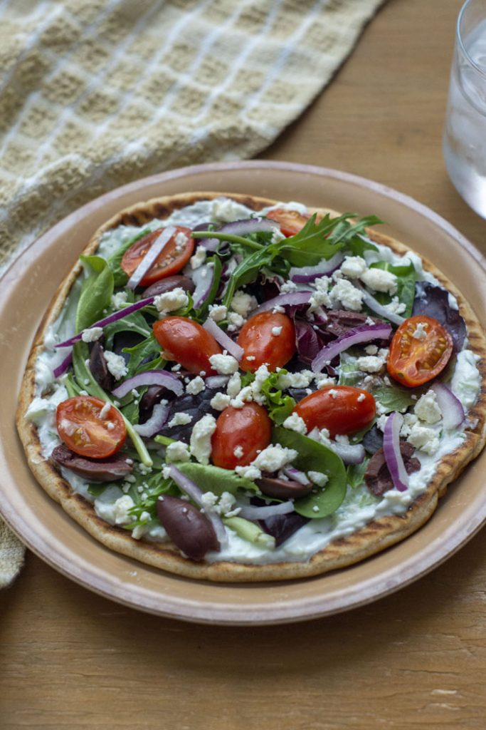 Open-Faced Greek Pita topped with sliced red onion, spinach, tzatziki sauce, sliced tomatoes, feta cheese, and greek olives on a tan plate next to a brown towel and glass of water