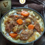 Guinness Beef Stew over a bed of mashed potatoes in a brown bowl with a bottle of Guinness beer and a brown and white towel behind all on a wooden surface (vertical with title overlay)