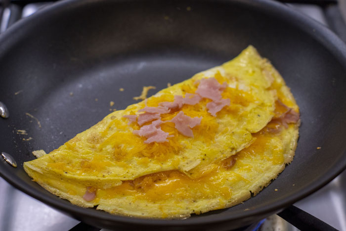 Ham and Cheese Omelet cooking in a skillet over a gas stovetop