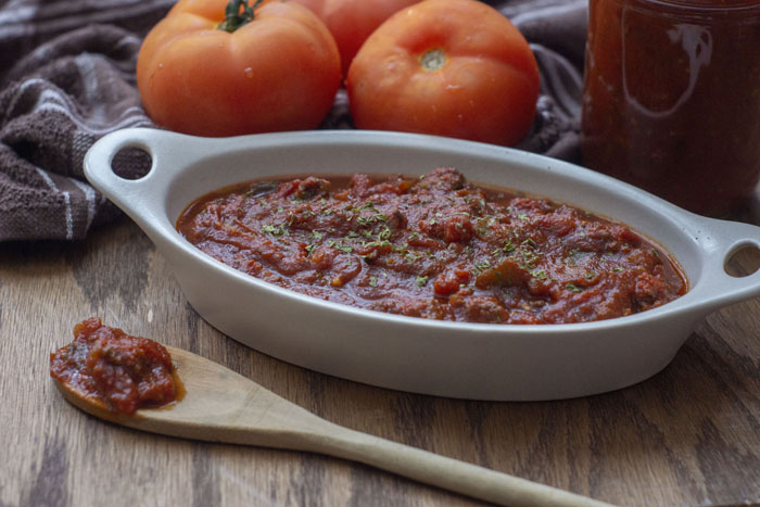 Meaty Marinara Sauce in a shallow white serving dish with a wooden spoon lifting a scoop next to three tomatoes on a brown towel and a jar of more sauce to the side all on a wooden surface