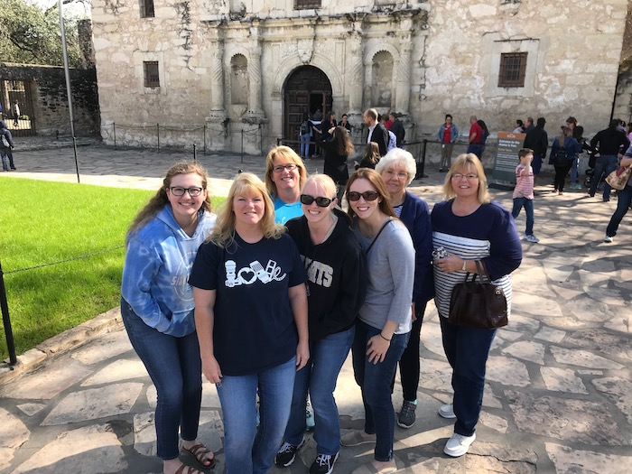Group of 7 women together in front of the Alamo in San Antonio, Texas