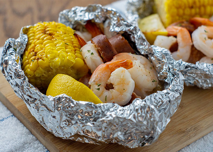 Shrimp boil foil wrap on a bamboo platter on a white and blue towel on a wooden surface