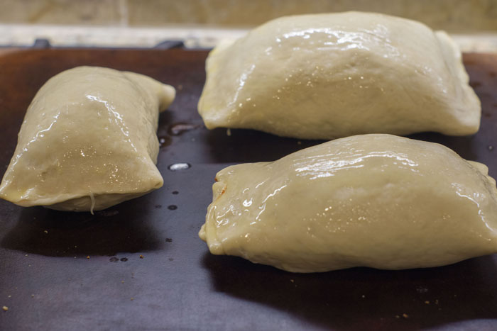 Rolled Stromboli dough covered with melted butter on a dark baking stone