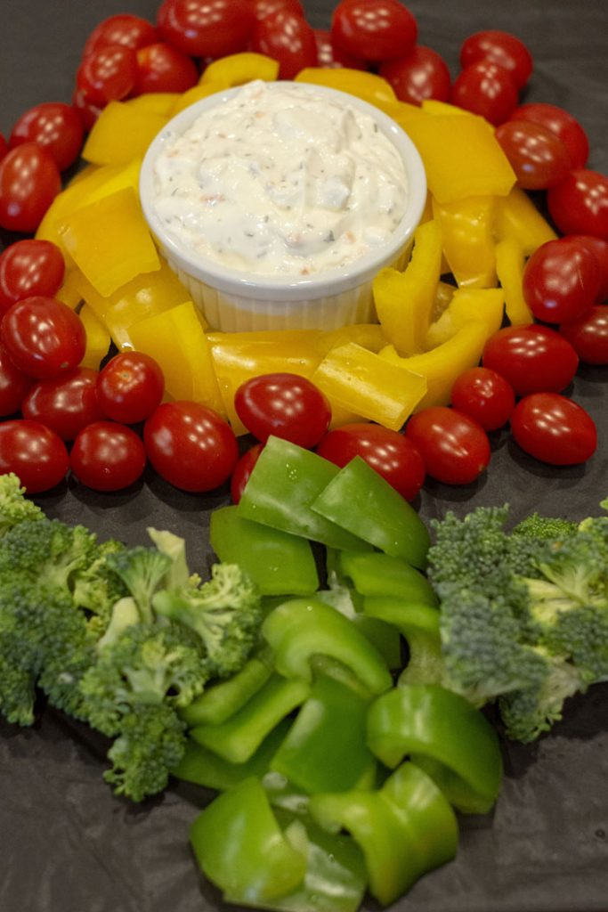 Super Mario fire flower vegetable flower with a white bowl of ranch dip surrounded by sliced yellow pepper then grapes tomatoes with sliced green pepper for the stem and broccoli leaves on a black tablecloth