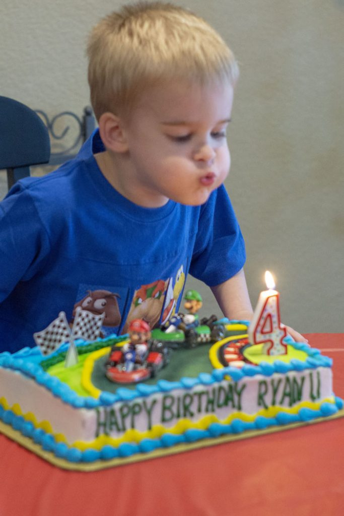 Young boy blowing out a number 4 candle on a mario kart birthday cake