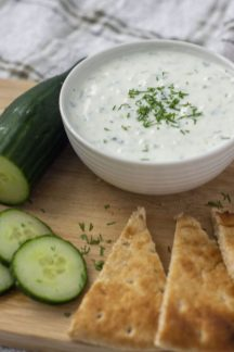 Tzatziki Sauce from Scratch garnished with dill in a large white bowl next to a partially sliced cucumber and slices of pita bread on a bamboo surface (vertical)
