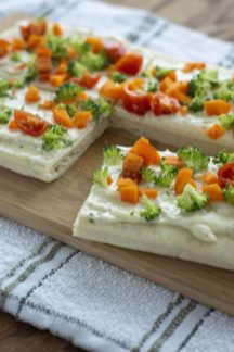 Veggie pizza with a square cut out on a bamboo tray on top of a white and brown towel on a wooden surface (vertical)