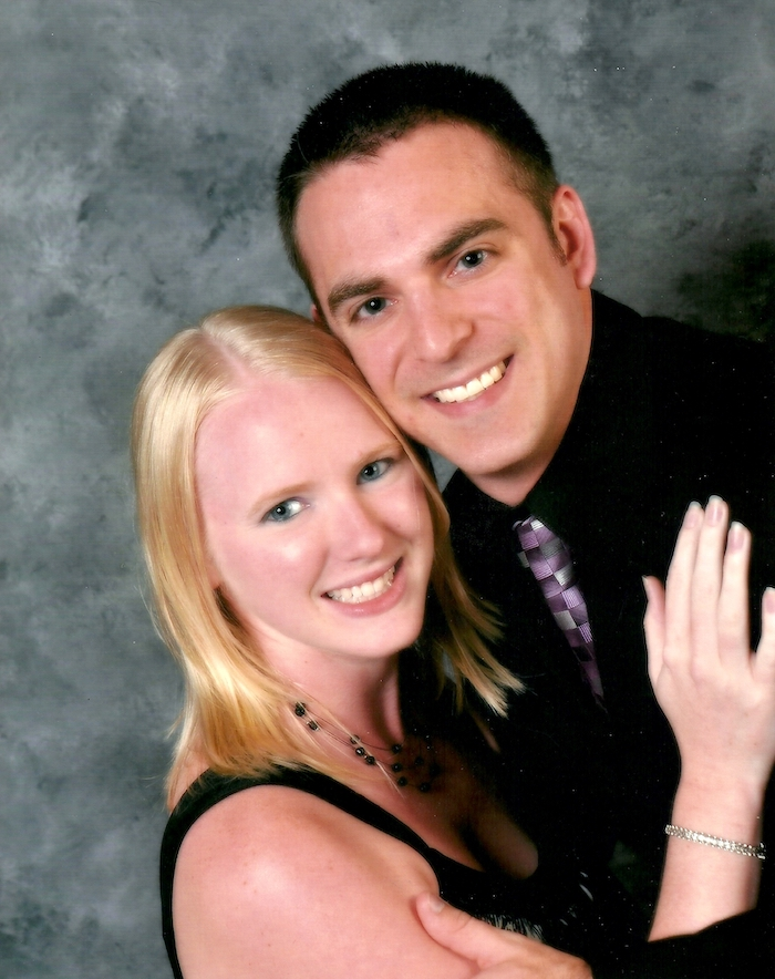 Man and woman posed for a professional photo in front of a grey backdrop