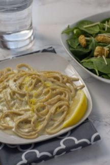 Creamy Lemon Pasta with a slice of lemon on a white plate with a grey napkin underneath and a salad and glass of water in the background on a white marble surface (vertical)