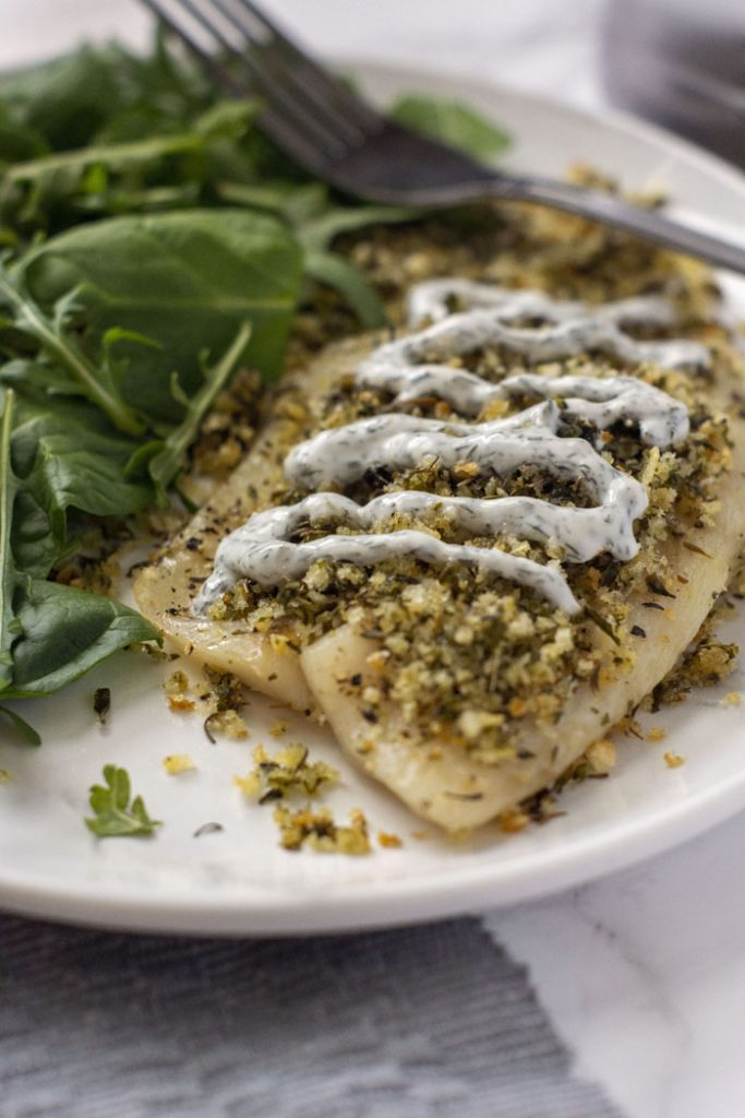 Dijon-Herb Tilapia close up on a white plate with a salad next to it (vertical)