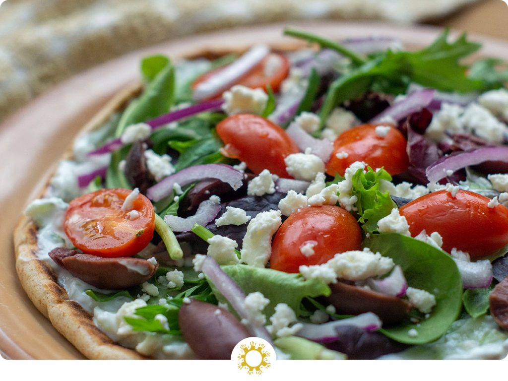 Open-Faced Greek Pita topped with sliced red onion, spinach, tzatziki sauce, sliced tomatoes, feta cheese, and greek olives on a tan plate (with logo overlay)