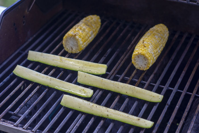 Sliced zucchini and corn on the cob cooking on a grill