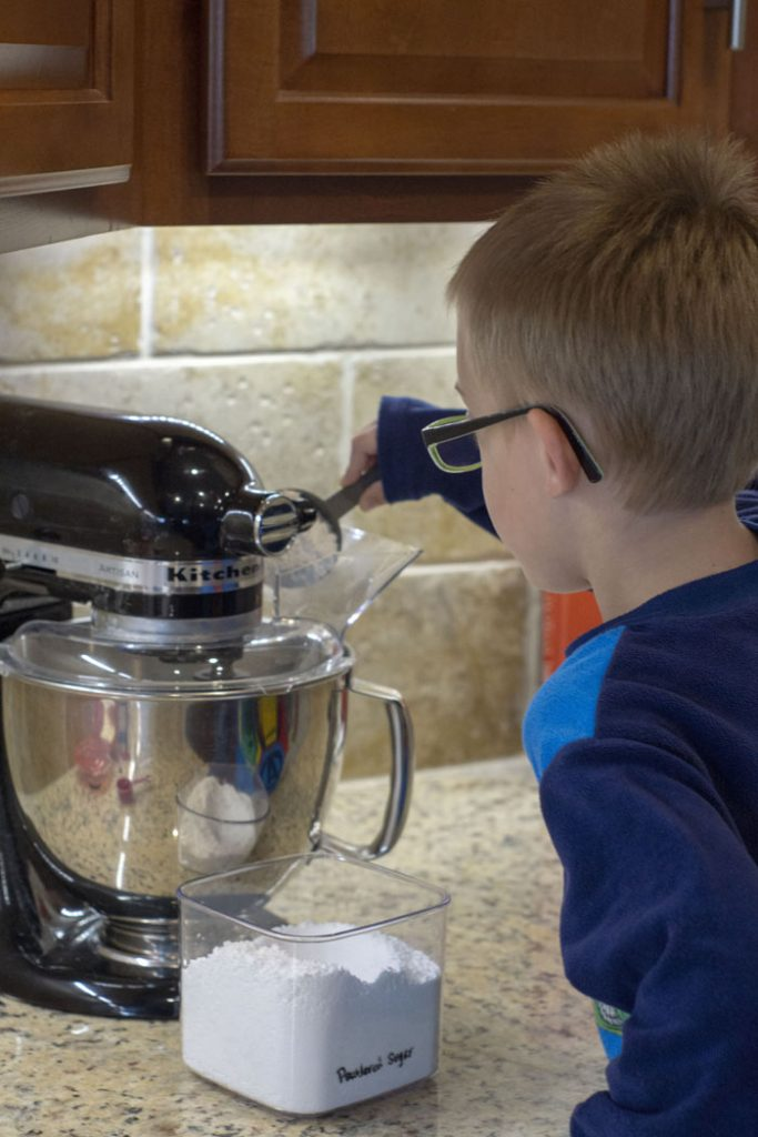 Young boy pouring powdered sugar into a stand mixer bowl