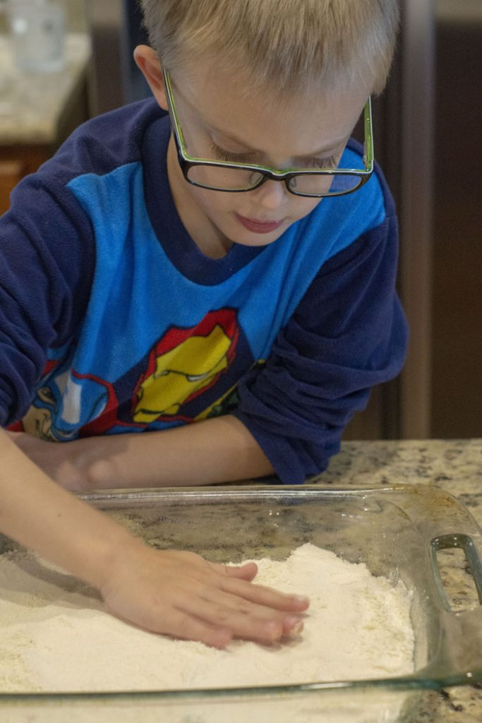 Young boy using his hands to pat down the crust in a large glass baking dish