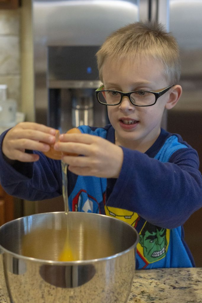 Young boy cracking an egg over a stainless steel bowl