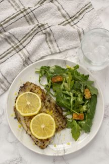 Top-down view of Lemon Rosemary Tilapia on a marbled plate with salad beside it on a grey marbled surface with a towel and glass of water (vertical)