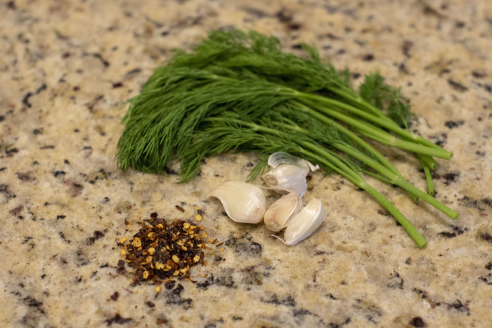 Ingredients for making dill pickles: fresh dill, garlic, and red pepper flakes