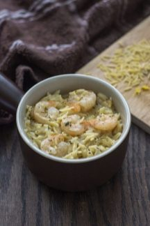 Shrimp Orzo with Lemon in a brown and white dish with a wooden board covered with orzo noodles all on a wooden surface (vertical)