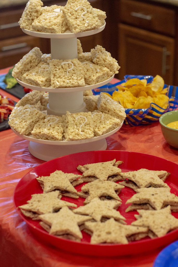 Super Easy Super Mario Themed Food with question block rice krispies and star shaped sandwiches on a red tablecloth