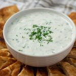 Tzatziki Sauce from Scratch garnished with dill in a large white bowl surrounded by slices of pita bread (vertical with title overlay)