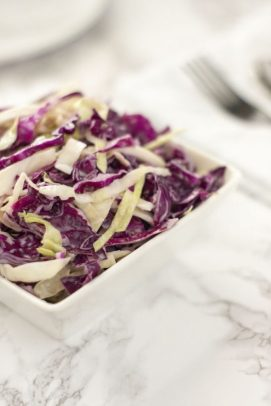 Coleslaw in a square white bowl on a white and grey marbled background (vertical)