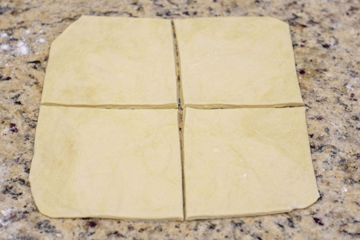 Puff pastry rolled out on a granite countertop cut into quarters