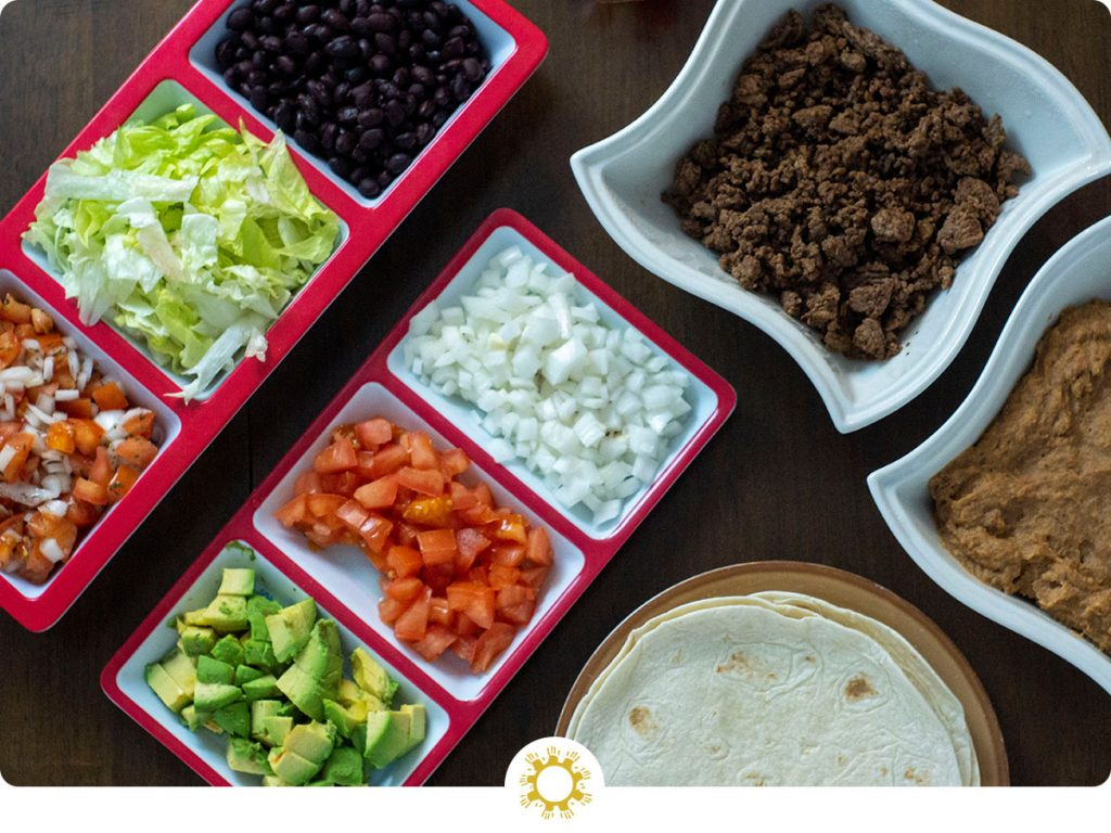 Taco bar on a wooden surface with multiple dishes of ingredients (logo overlay)