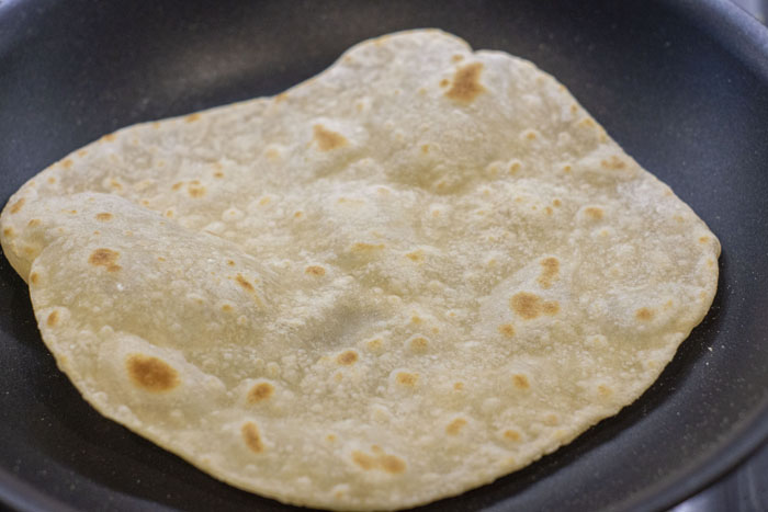 Tortilla shell cooking in a pan