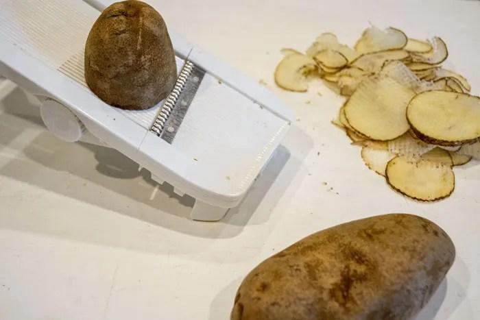 Potatoes on a mandolin slicer