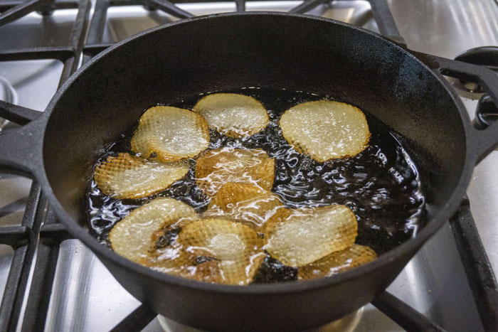 Potato chips in a cast iron pan full of cooking oil over a gas stovetop