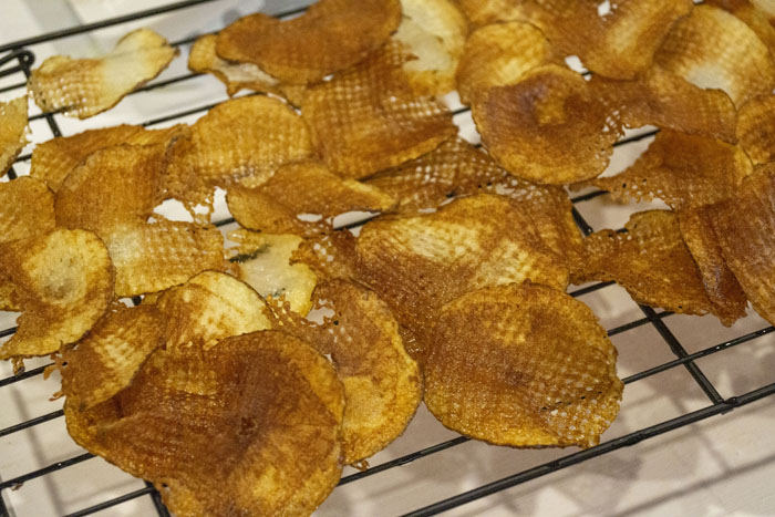 Potato chips on a wire rack after being cooked
