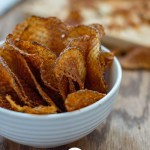 BBQ Waffle Chips in a small white bowl with crumbs in the background (with title overlay)
