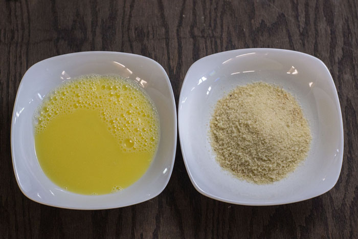Egg in one bowl and panko in another bowl on a wooden countertop