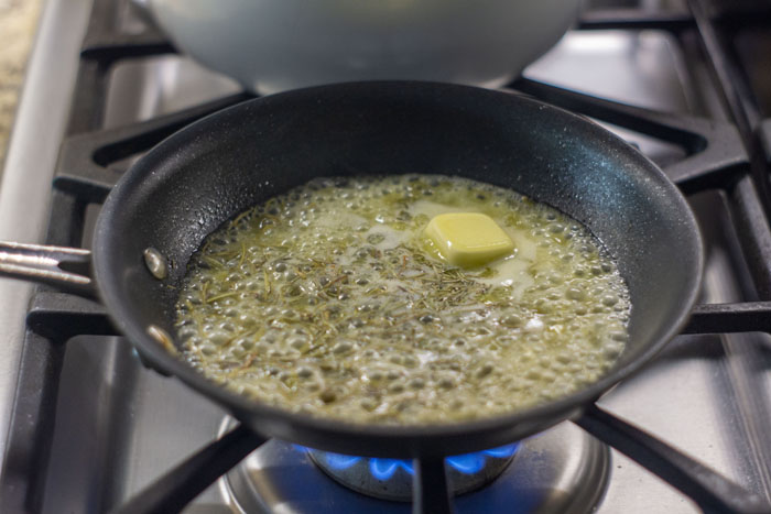 Butter, broth, and seasonings in small skillet on a gas stovetop