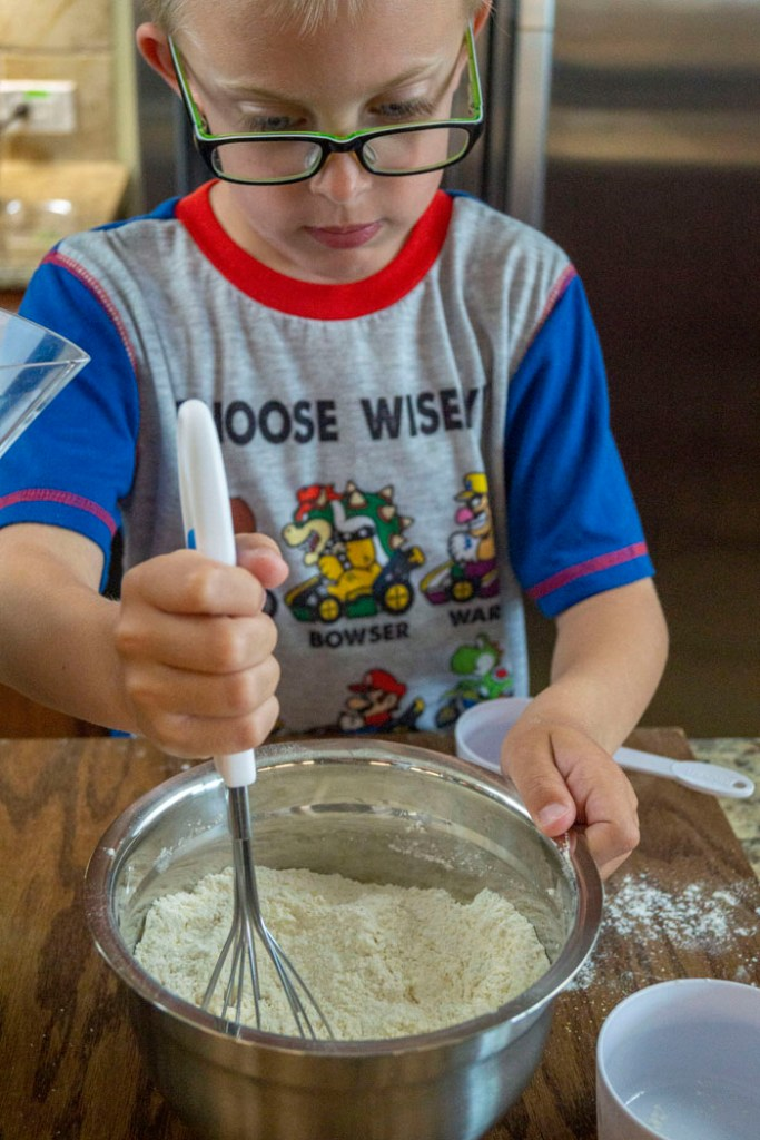 Young boy whisking ingredients in a stainless steel bowl